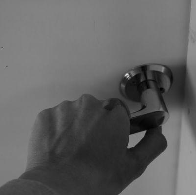 Blodig hand griper tag om ett dörrhandtag.
