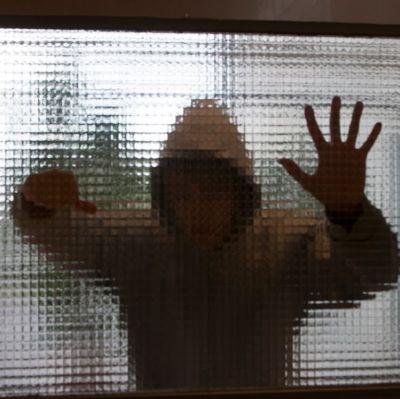 Anonym ung beter sig våldsamt bakom en glasvägg.