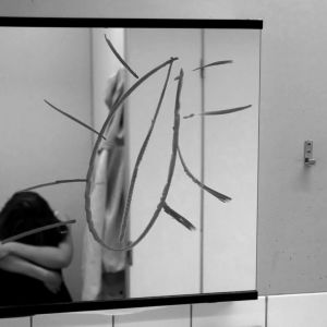 Flicka sitter inne på toaletten med nerböjt huvud. Någon har ritat en kyrkbåt i badrumsspegeln.