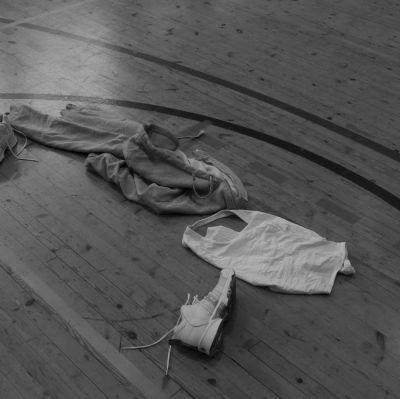 Kläder ligger på golvet i en gymnastiksal.