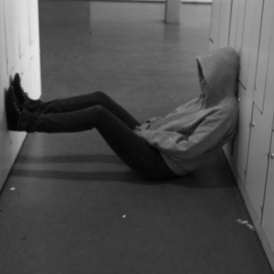 Ensam ungdom sitter på golvet.