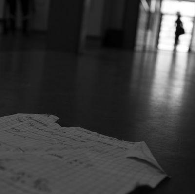 Papper ligger på golvet i en korridor.