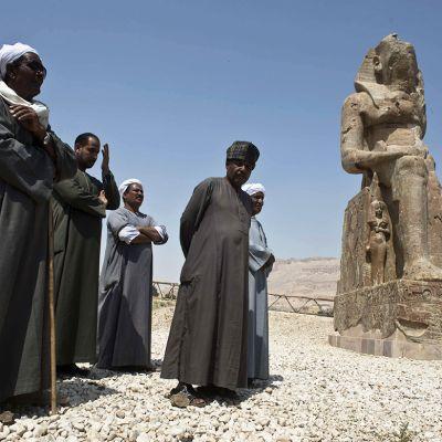 Kaapuihin pukeutuneita miehiä seisomassa vastapaljastetun farao Amenhotep III:ta esittävän patsaan vierellä Luxorissa, Egyptissä 23. maaliskuuta 2014.