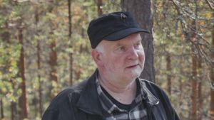 Mies musta lippalakki päässä ja ruutupaita ja musta takki päällä metsässä