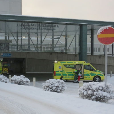 Entrén till centralsjukhuset i Rovaniemi. Utanför står två ambulanser. Det ligger snö på marken.