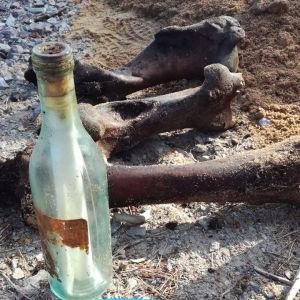 Ett bildmontage av två bilder. Bilden till vänster är ett gammalt fotografi av en man i militärkläder. Bilden till höger visar gamla ben som ligger på marken intill en flaskpost.