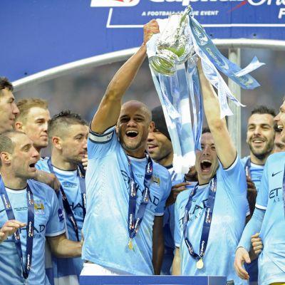 Manchester Cityn Vincent Kompany ja Samir Nasri nostavat liigacupin mestaruuspokaalin ilmaan.