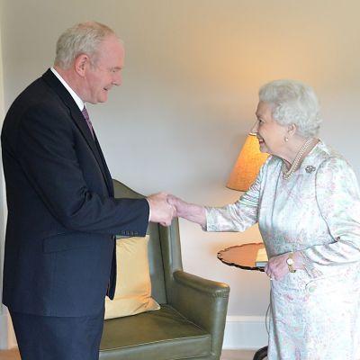 Hymyilevät Martin McGuinness ja kuningatar Elisabet kättelevät.