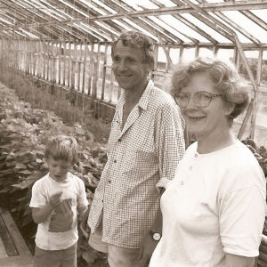 Lapsi, mies ja nainen kasvihuoneessa.