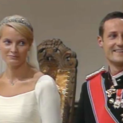 Mette-Marit ja Haakon istuvat kirkossa häävaateissaan.