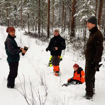 Haapaveden kylä ry:n jäsenet suunnittelevat latua lumisessa metsässä.