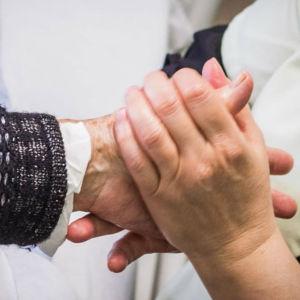 Vårdare håller patients hand.