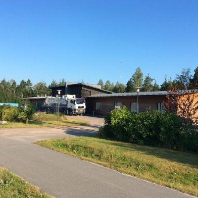 Envåningsbyggnad med träfasad och persiennerna fördragna. En sugtömningsbil står utanför byggnaden. Sommar.
