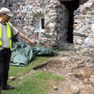 Man i reflexväst och skärmmössa står vid en arkeologisk utgrävning och pekar på stenar i en uppgrävt ruta. Stenmurar.