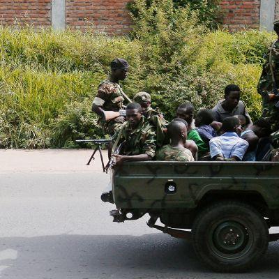 Sotilaita ja vangittuja autossa.