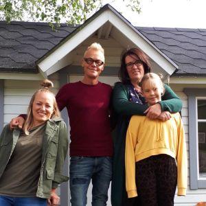 Fyra personer framför en lekstuga