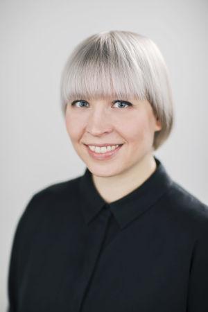 En leende kvinna mot en vit bakgrund.