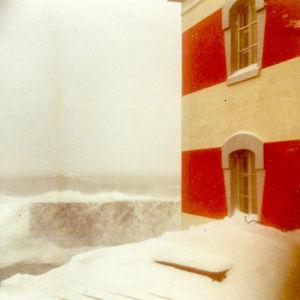 Talvimyrsky raidallisella majakalla, meri huuhtoutuu muurin ylitse, lunta on pakkaantunut ikkunan alle.