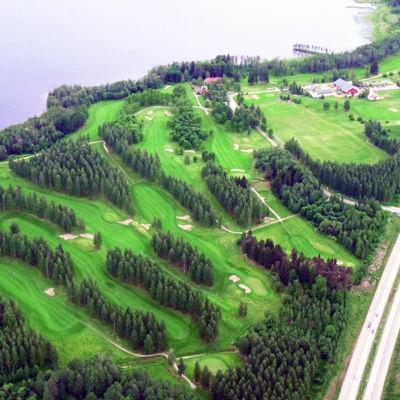 Ilmakuva vihreästä golfkentästä järven rannalla.