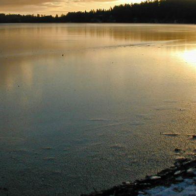 Pieni järvi auringonlaskun aikaan ohuessa jääpeitteessa alkutalvesta