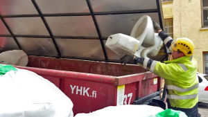 Rakennusmies heittää wc-pönttöä roskalavalle.