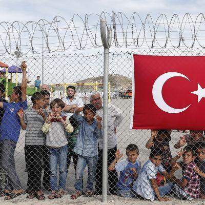 Joukko syyrialaisia pakolaisia seisoo piikkilanka-aidan taka. Aidassa roikkuu Turkin lippu.