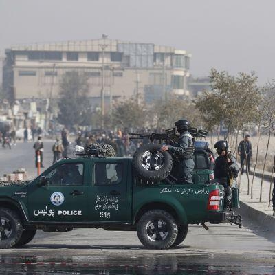 Vihreä poliisiauto, jonka katolla on automaattiasetta kantava poliisi.