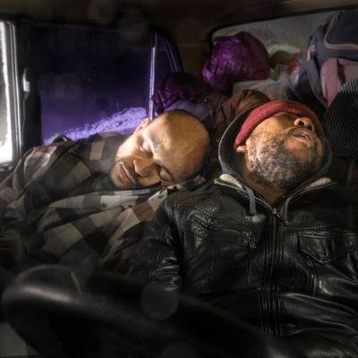 Kaksi miestä nukkuu autossa