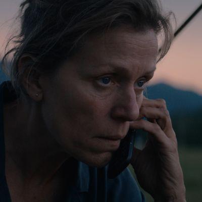 Mildred sitter och talar i sin mobil i ett öppet landskap.
