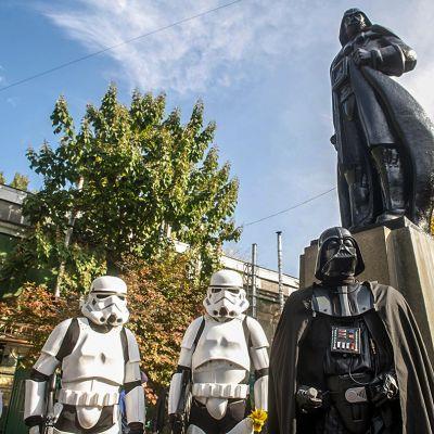 Darth Vaderia esittävä patsas ja kolme Tähtien sota -elokuvien hahmoja esittäviä ihmisiä.