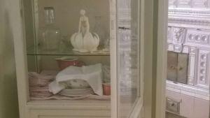 Ett naturvitt tandläkarskåp med kristallglas och porslin.