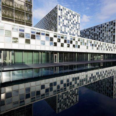 Suuri valkoinen rakennus, joka heijastuu sen edessä olevaan veteen, Rakennuksen seinät ovat ikkunoita, joista osa on valkoisia ja osaan heijastuu sininen taivas.