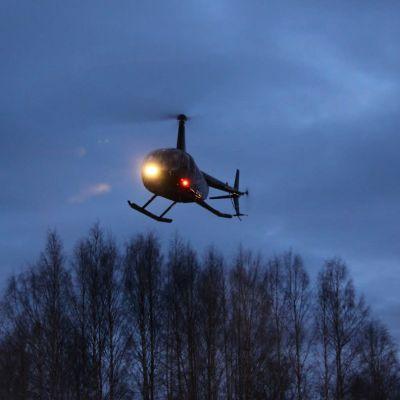 Helikopteri lentää puiden latvojen yläpuolella