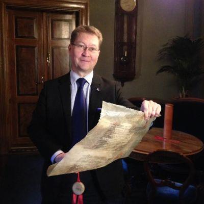Mika Akkanen håller i pergamentet med julfreden.