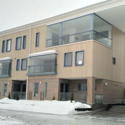 En fastighet med lokaler i flera våningar. Fasaden är i ljust trä. Marken är täckt av snö.