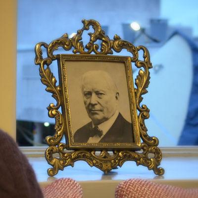Porträtt på museichef Kai Kartio (suddig) med foto på Amos Andersson i bakgrunden (skarp).