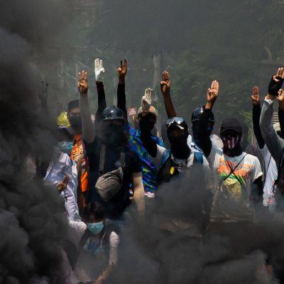 Mielenosoittajia savun keskellä Yangonissa, Myanmarissa.