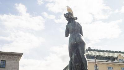 Havis Amanda på en solig dag. I bakgrunden syns blå himmel. En mås sitter på statyn.