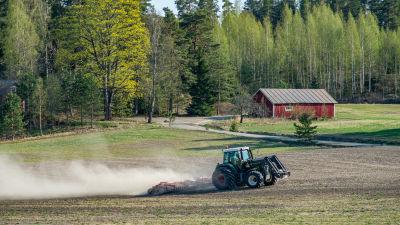En grön traktor harvar jorden en vårdag där löven spricker ut i träden och en röd lada lyser i solen.