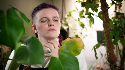 En kvinna med färgglatt hår i flätor står bland massa växter.