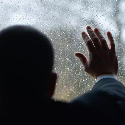 En man tittar ut genom fönstret.