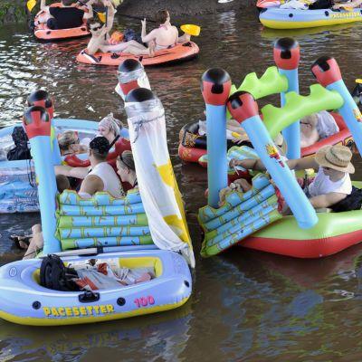Ihmisiä värikkäissä kumiveneissä ja lastenaltaissa joella.