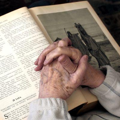 Kädet ristissä Raamatun päällä.