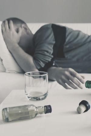 Man ligger i en soffan med handen för ansiktet och flera tomma spritflaskor på bordet.