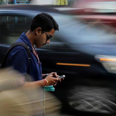 Intialainen mies näpyttelee puhelintaan kadulla.