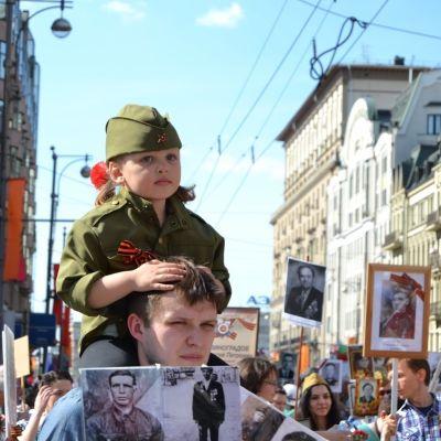 Sotilasasuun puettu pikkutyttö miehen hartioilla.