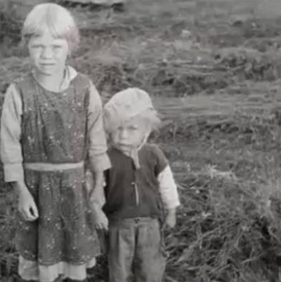 Storasyster som håller sin lillebror i handen