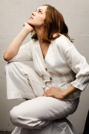 Punertavahiuksinen nainen pukeutuneena valkoiseen housupukuun on kyykistyneenä, katsoo vasempaan yläviistoon omaan käteensä nojaten.