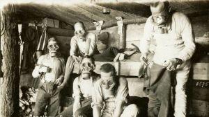 Postkort med mänskor som bär gasmasker i en gasalarmssituation under första världskriget.