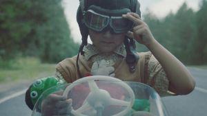 En pojke sitter i en leksaksbil med en gammaldags hjälm på huvudet.